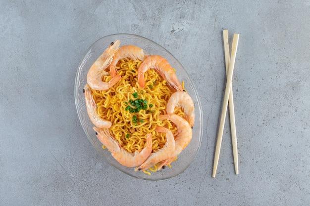 Gamberetti e noodle su un piatto di vetro accanto alle bacchette, sulla superficie di marmo.