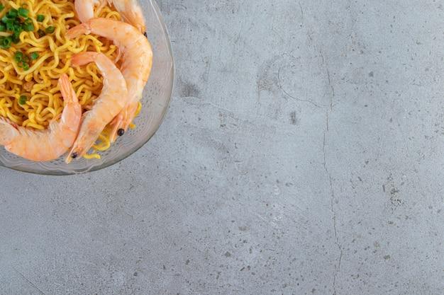 Gamberetti e noodle su un piatto di vetro, sullo sfondo di marmo.