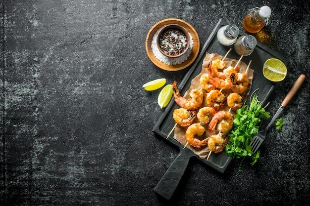 黒の素朴なテーブルにパセリ、スパイス、ライムスライスを添えた串焼きのエビ
