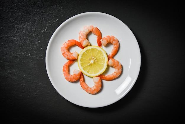 Shrimps prawns served decorate seafood plate and lemon on dark background