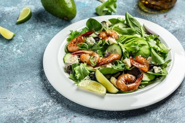 Салат из креветок, авокадо, сыр с плесенью и копченые креветки. домашний вегетарианский салат из креветок. концепция морепродуктов. вкусный овощной микс из листьев, креветки на гриле.
