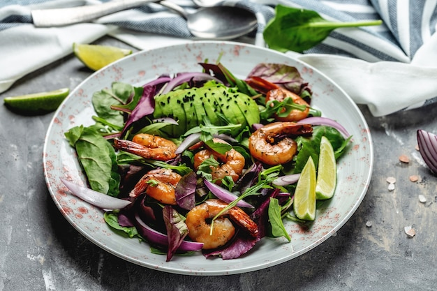 Салат из креветок, авокадо, лук и копченые креветки. домашний вегетарианский салат из креветок. концепция морепродуктов. вкусный овощной микс из листьев, креветки на гриле.