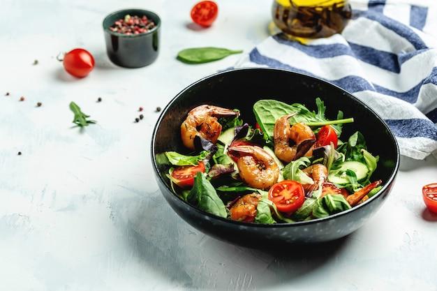 Салат из креветок, помидоры черри, огурец и смешанные листья, креветки на гриле. здоровая пища. чистая еда. место для текста, вид сверху.