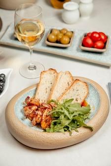 Креветки с рукколой и хлебом подаются с белым вином