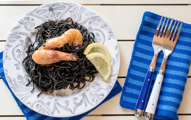 Shrimps with black seaweed and slices of lemon