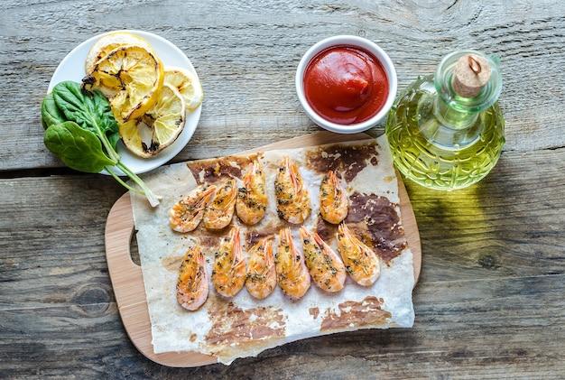 Креветки с лимоном и острым соусом на деревянном столе