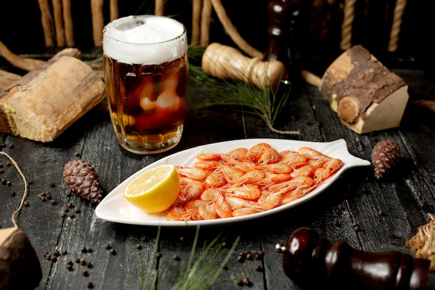 Shrimps with lemon slice and glass of beer