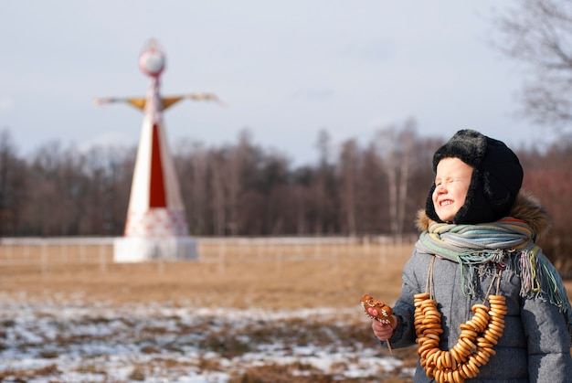 Масленица (масленица) концепция. фанни лицо мальчика с рогаликами. на открытом воздухе в зимнее время.