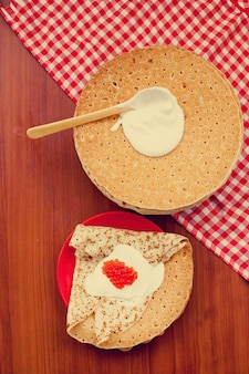 Shrovetidemaslenitsaフェスティバルの食事。木製の壁に生クリームと赤キャビアとロシアのパンケーキブリニ