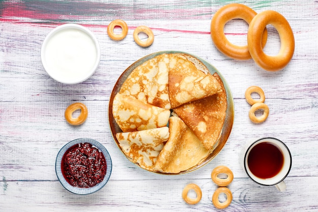Shrovetide maslenitsa festival meal. russian pancake blini with raspberry jam, honey, fresh cream and red caviar,sugar cubes,cottage cheese,bubliks on light background