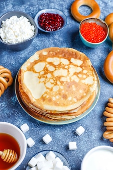 Shrovetide maslenitsa festival meal. russian pancake blini with raspberry jam, honey, fresh cream and red caviar, sugar cubes, cottage cheese on dark