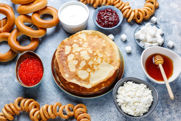 Shrovetide maslenitsa festival meal. russian pancake blini with raspberry jam, honey, fresh cream and red caviar, sugar cubes, cottage cheese on light