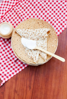 Shrovetide、木製の背景にサワークリームとパンケーキ。上からの眺め。料理のコンセプト、マルディグラ