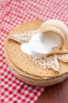 Shrovetide、木製の壁にサワークリームを添えたパンケーキ。上からの眺め。料理のコンセプト、マルディグラ