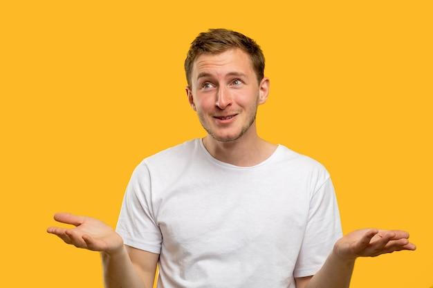 Жест пожатия плечами. и что. бестолковый человек, поднимающий плечи, улыбаясь, изолирован на оранжевой стене.