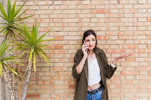 携帯電話shruggingで話すレンガの壁に立っている美しい若い女性