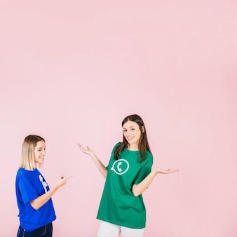 ピンクの背景にshrugging彼女の友人を指す笑顔の女性