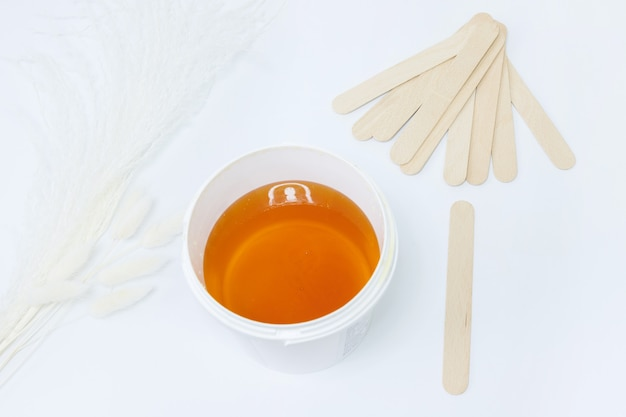 Shugaring paste with a stick on a white background. shugaring accessories