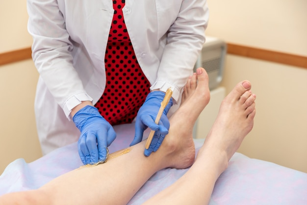 Shugaring procedure hair removal in a beauty salon close up