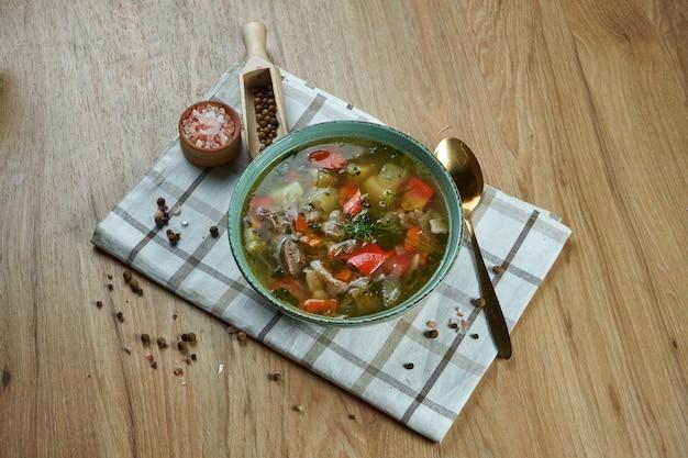 Шурпа - это традиционный, густой и питательный суп с кавказа. аппетитный суп из баранины с помидорами, перцем, луком и картофелем в синей миске. закрыть