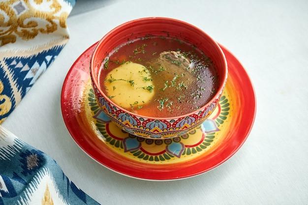 白い表面のボウルにシュルパスープ。子羊とスパイスが入ったグルジアのスープ。コピースペース。グルジア料理。
