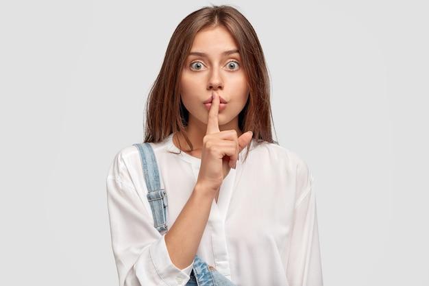 黙って、黙って!真面目な素敵な女性は、白い特大のシャツとデニムのオーバーオールを着て、白い壁にポーズをとって、秘密情報を秘密にしておくように頼みます。陰謀の概念