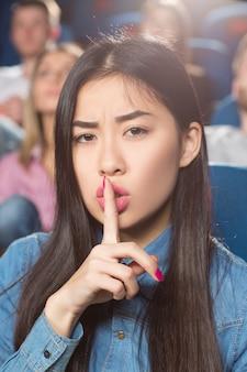 映画館で映画を見ながら彼女の唇に彼女の指でshushingジェスチャーを作るアジアの女性