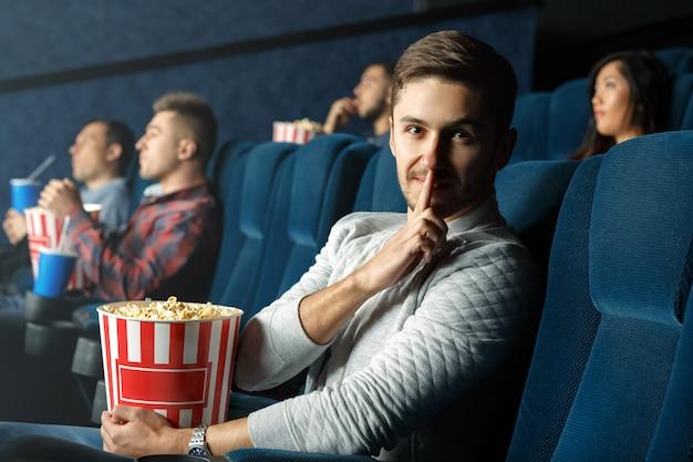 静かにしてください。映画館で若い男性作るshushingジェスチャー