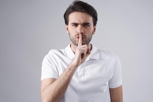 白人男性が白い背景で隔離shushingをポーズします。