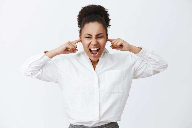 Zitti tutti. ritratto di donna di affari afro-americana femminile in difficoltà intensa in camicia bianca, gridando mentre chiude le orecchie con le dita, essendo incazzato e arrabbiato, in piedi in posizione rumorosa
