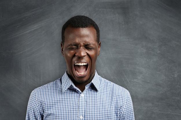 黙れ!目を閉じ、口を大きく開いて、不従順な生徒に向かって叫び、沈黙を求めている怒り狂うアフリカの高校教師のヘッドショット。