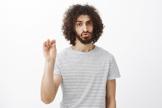 Shut up please. portrait of bothered and pissed off handsome male model with curly hair and beard, showing keep quiet gesture with palm