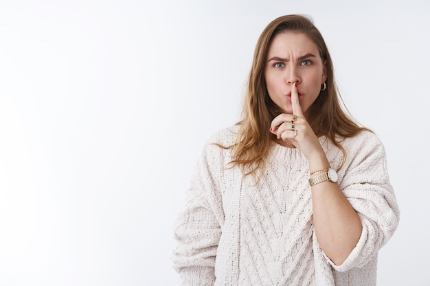 Shut up shh. irritated bossy displeased angry womans shushing you not talk quit scream loud holding index finger on lips frowning demanding hide secret not slip word, standing white background