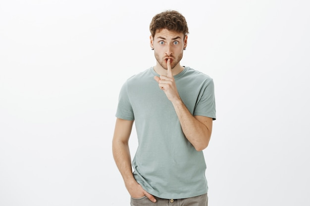 Shut up, do not speak. portrait of displeased angry male teacher in casual t-shirt, lifting eyebrows from anger, saying shh while showing shush gesture and staring scary