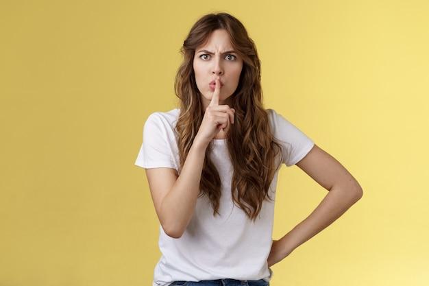Закрой рот, не разговаривай во время концерта. серьезно выглядящая строгая недовольная взрослая сестра требует сидеть тихо, замолчать, держать указательный палец, прижать губы, нахмуриться, сердиться, замолчать желтый фон
