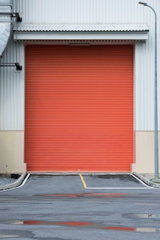 Shutter door or roller door orange color and concrete floor outside factory building