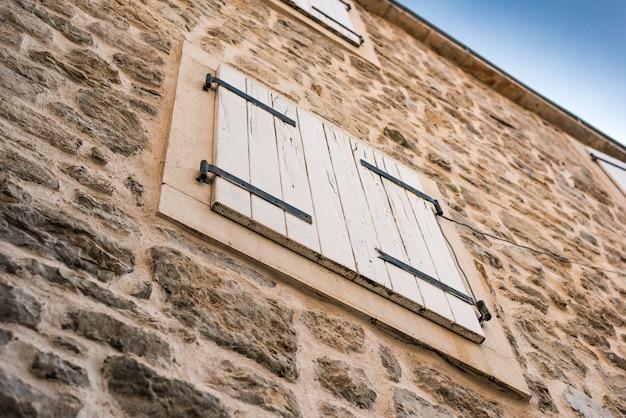 Окно с ставнями в древнем каменном городе
