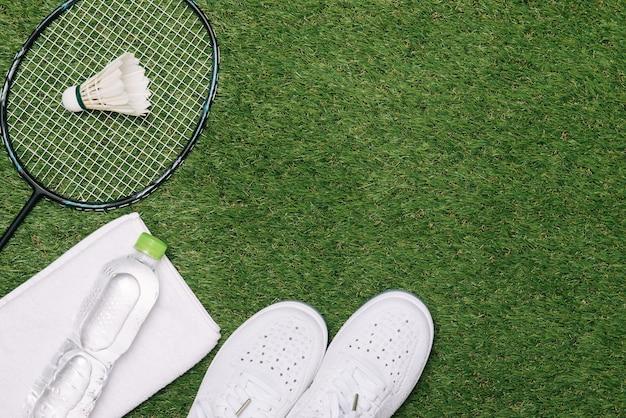Ракетка для волана и бадминтона с обувью, водой и полотенцем на фоне травы.