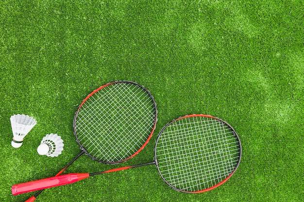 Shuttlecocks with red badminton on green turf backdrop