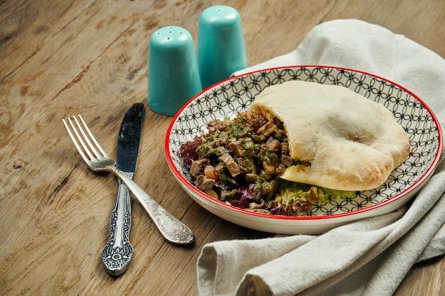 Вкусная уличная еда - лаваш с помидорами, огурцами и говядиной в голубом блате на деревянной поверхности. греческая кухня крупным планом зрения. shwarma