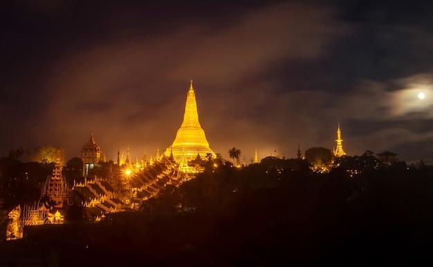 Shwedagon pagoda는 미얀마 랑군에서 밤에 아름다운 물 반사를 내려다보고 있습니다.