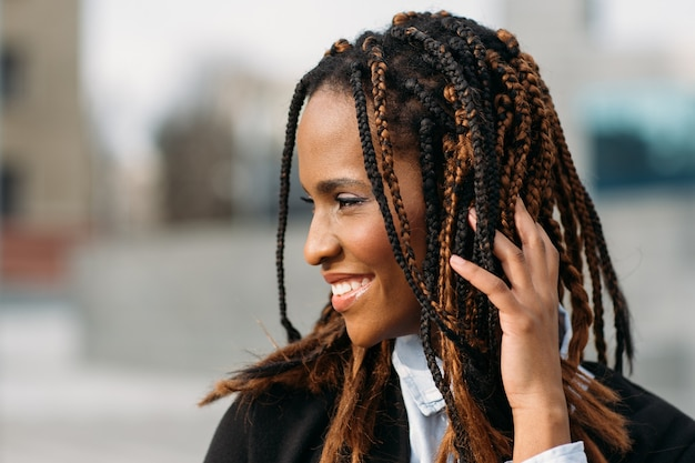恥ずかしがり屋のアフリカ系アメリカ人の女性。幸せなモデルの笑顔。選択的な焦点の屋外、ファッションヘアスタイル、幸福の概念で笑っている若い黒人女性
