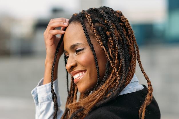 恥ずかしがり屋のアフリカ系アメリカ人の女性。幸せなモデルの笑顔。選択的な焦点の屋外、ファッションの髪型、幸福の概念に笑みを浮かべて若い黒人女性