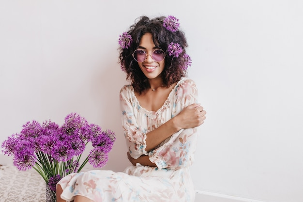 Shy african girl in white dress posing with alliums. indoor photo of cheerful black young woman in glasses sitting.