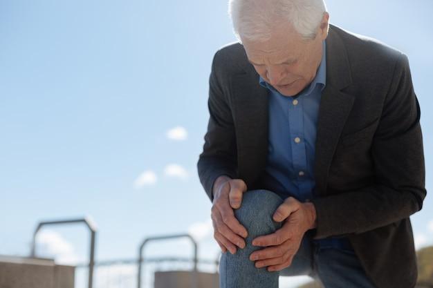 Застенчивый стареющий испуганный мужчина выражает дискомфорт и волнуется, испытывая сильную боль