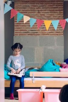 Застенчивая и замкнутая маленькая девочка держит свои игрушки