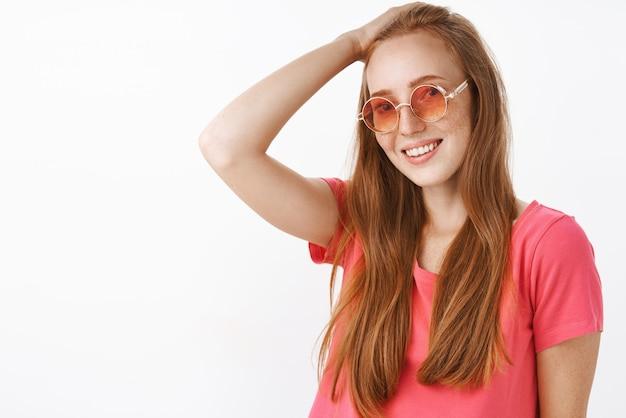 Застенчивая и нежная очаровательная рыжая дама с веснушками в модных солнечных очках и розовой блузке расчесывает волосы рукой на голове и дружелюбно улыбается