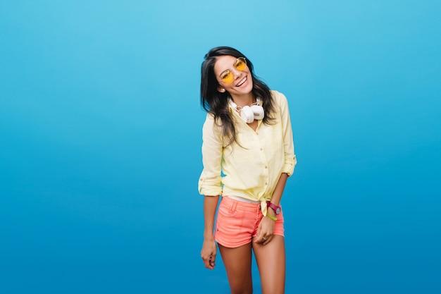 快適なポーズでポーズをとる流行の黄色いジャケットの恥ずかしがり屋の黒髪のヨーロッパの女の子。良い日に冷えるヘッドフォンでブルネットの白人女性の屋内写真。