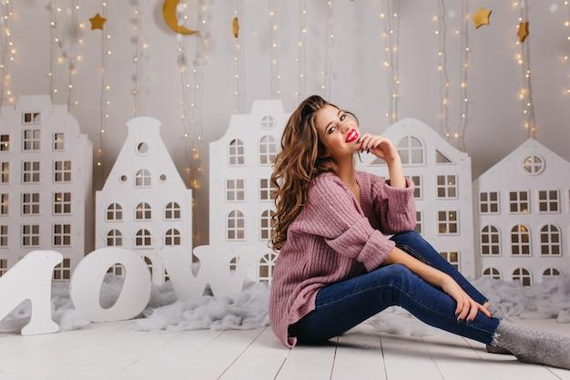 핑크 니트 스웨터에 바닥에 앉아 수줍은 갈색 머리 소녀. 하얀 풍경을 배경으로 한 아름다운 벽의 전신 사진.