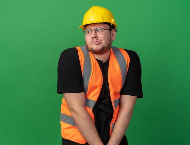 建設ベストと安全ヘルメットの恥ずかしがり屋のビルダーの男は混乱して脇を見て
